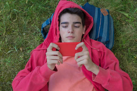 student lying in the field on the backpack with the mobile phone