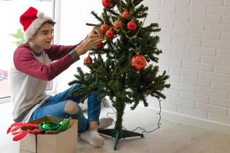 young man with santa claus hat decorating the christmas tree at home