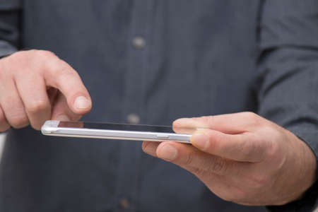businessman hands with mobile touch phone, closeup view