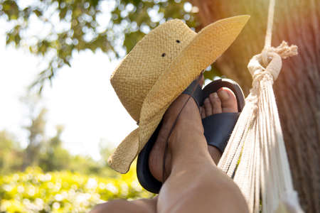 feet in the hammock with hat at sunset in summer, vacation 版權商用圖片