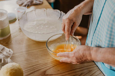 cook mixing and whisking eggs and ingredients for sweets and pastries