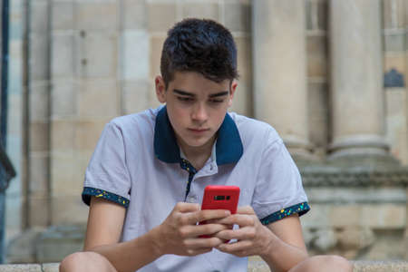young teenage man with mobile phone outdoors 스톡 콘텐츠