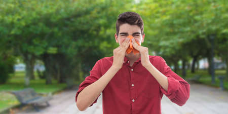 young boy or teenager with a handkerchief for cold or allergy Stockfoto