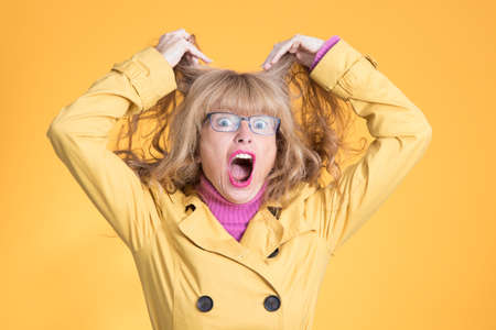 portrait of woman with expression of stress and despair with glasses on color background