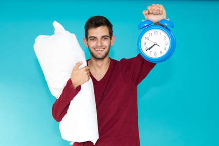 young man with pajamas and alarm clock with pillow isolated on color background Banco de Imagens