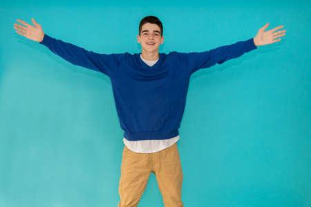 junger Mann im Teenageralter isoliert auf farbigem Hintergrund mit offenen Armen Standard-Bild