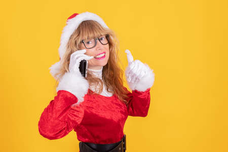 santa claus woman with mobile phone isolated on color background Stock Photo