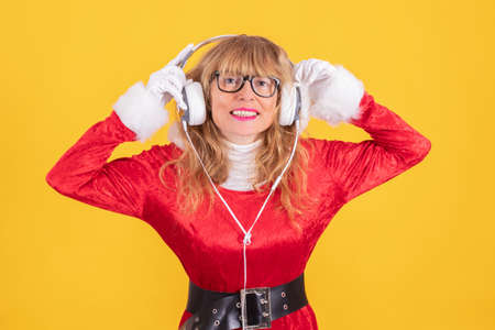 woman in santa claus costume and headphones isolated on color background