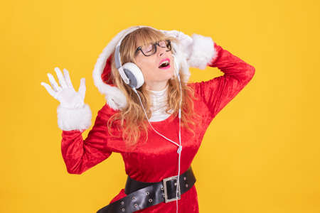 woman in santa claus costume and headphones isolated on color background Stock Photo