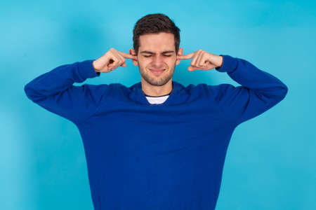 casual young man isolated on natural blue background