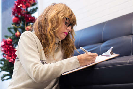 adult woman at home writing cards or congratulations with christmas decoration