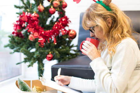 woman with coffee cup writing christmas congratulations