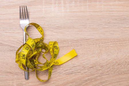 fork with tape measure, diet and weight loss concept