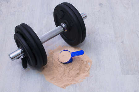 protein powder and dumbbell in the gym