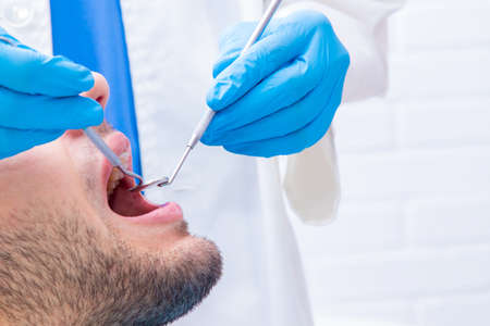 dentist with tools working on the patient's mouth Foto de archivo