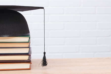 graduation cap and books on wood and white background