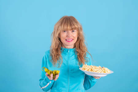 smiling woman with plate of pasta and measuring tape in color background