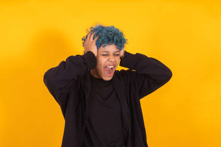young african american girl or woman isolated on yellow background with expression and blue hair