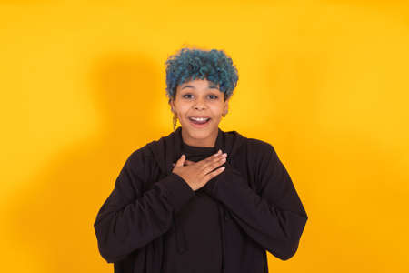 young african american girl or woman with blue hair isolated on yellow background