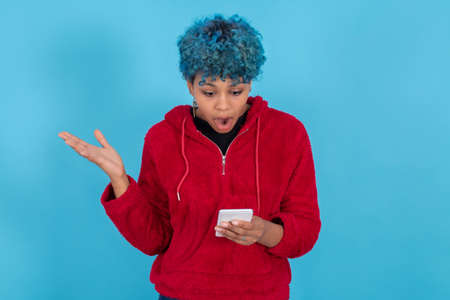 young girl or woman looking with surprise at mobile phone isolated on blue background