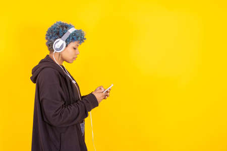 young girl with mobile phone and headphones isolated on color background Stok Fotoğraf