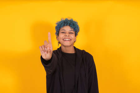 young african american girl or woman with blue hair isolated on yellow background Stock Photo