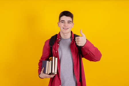 teenage student with books and school or university backpack isolated on color background