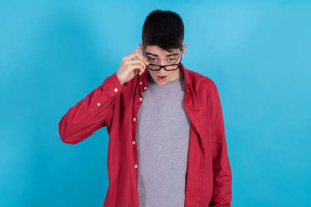 young man or teenage student isolated on color background with a gesture of amazement looking down Foto de archivo