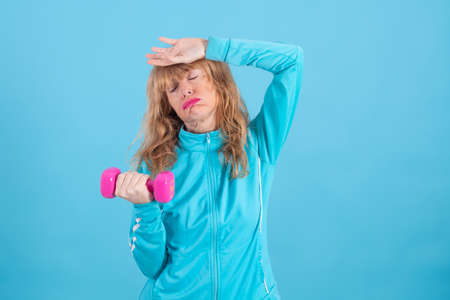 femme avec expression d'effort ou de fatigue avec des haltères d'exercice isolés sur fond bleu
