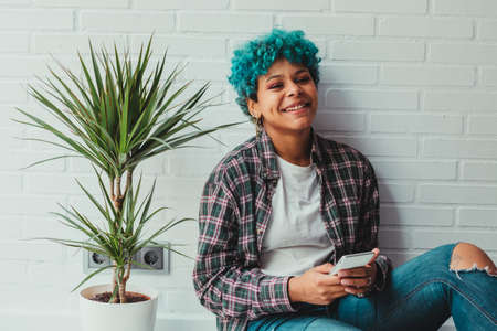 young african american woman or girl with blue hair with mobile phone in apartment with plant and brick background