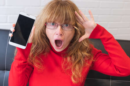 adult woman with mobile phone and expression of amazement or surprise