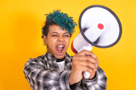 portrait of shouting girl with megaphone isolated on color background Imagens