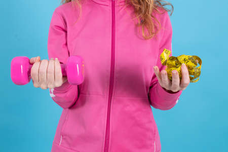 woman with gym weights and measuring tape, sport and losing weight