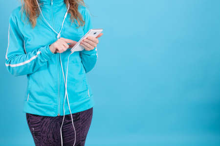 woman hands with mobile phone and sportswear on blue background