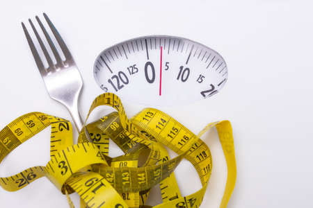 scale with measuring tape and fork, diet and weight loss concept