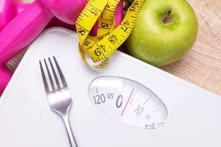 scale with measuring tape and fruit, diet and weight loss concept