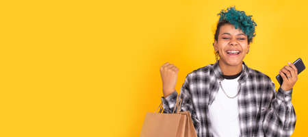 young girl with mobile phone and shopping bags isolated on yellow background