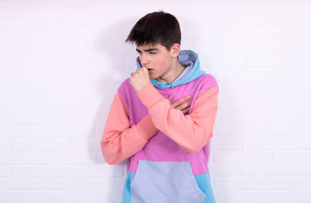 young teenage man with coughing or constipated expression Stockfoto