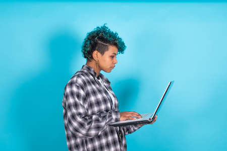 young african american woman with blue curly hair and laptop computer isolated on yellow background