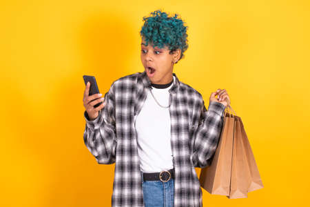 young brunette girl with shopping bags and mobile phone isolated on yellow background