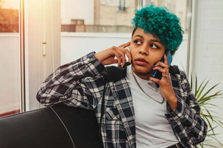 young woman or girl with mobile phone at home or apartment with blue hair afro american curl