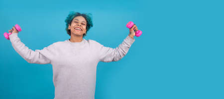 woman doing gymnastics with aerobics weights isolated on color background