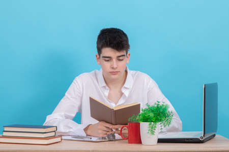 young male student at desk with book and computer studying Banco de Imagens