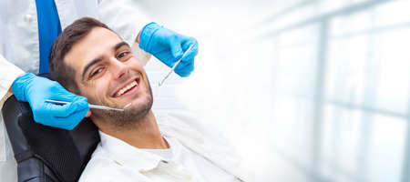 young man in the dental clinic with tools and hands of the dentist Stock Photo