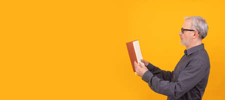 adult or senior man with book isolated on color background