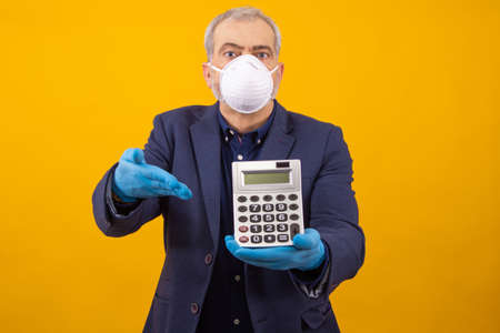 businessman with sanitary mask and calculator isolated on background Фото со стока