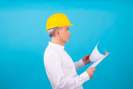 man isolated on color background with construction helmet