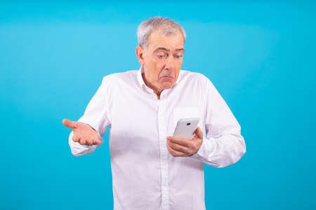 isolated adult or senior man with mobile phone and expression of incomprehension