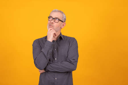 adult or senior man isolated on color background with thoughtful expression