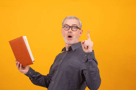 adult man with book or agenda and glasses with finger up pointing or warning